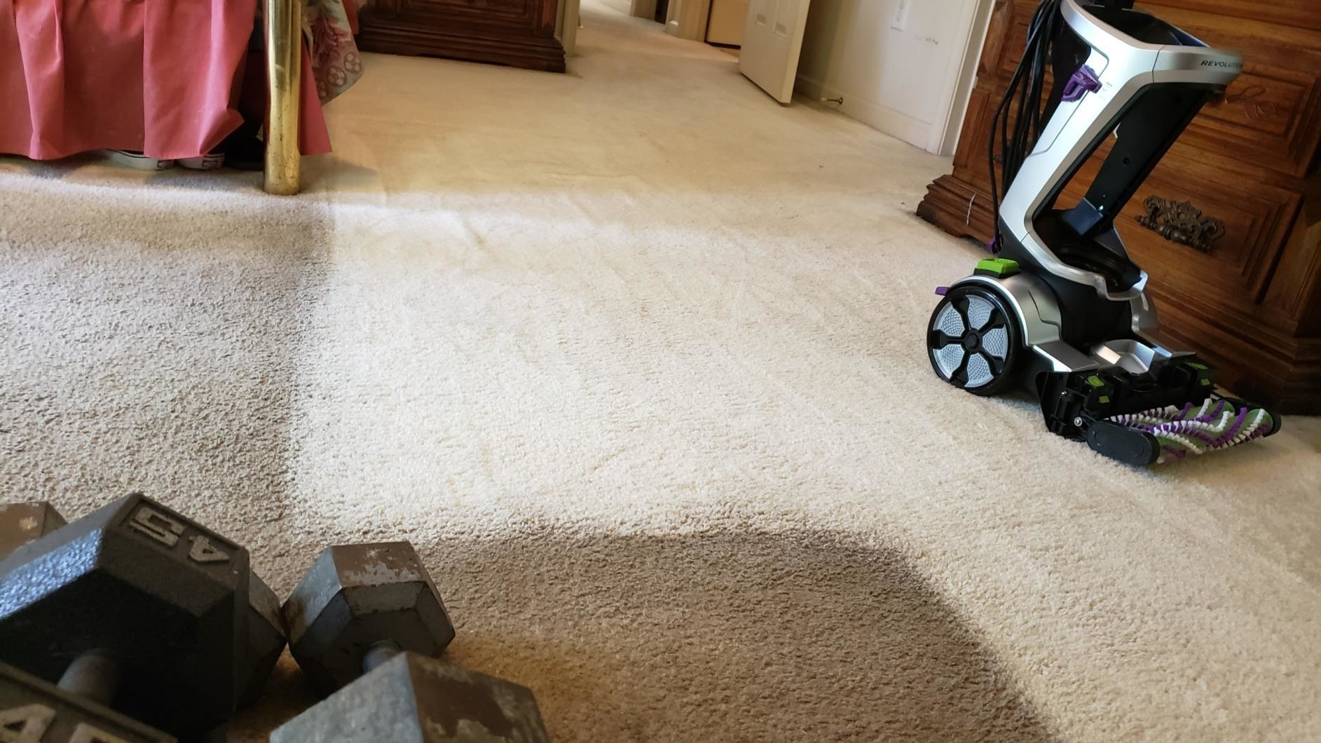 reviewer image of dirty and dark carpet next to clean and light carpet with the bissel pet pro on top