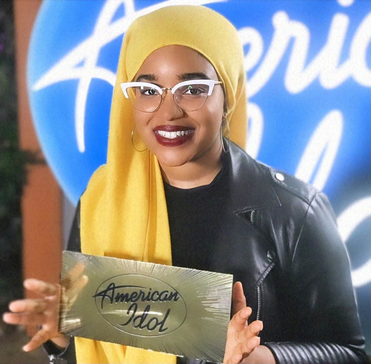 """Amira holds up a golden ticket with the """"American Idol"""" logo on it"""