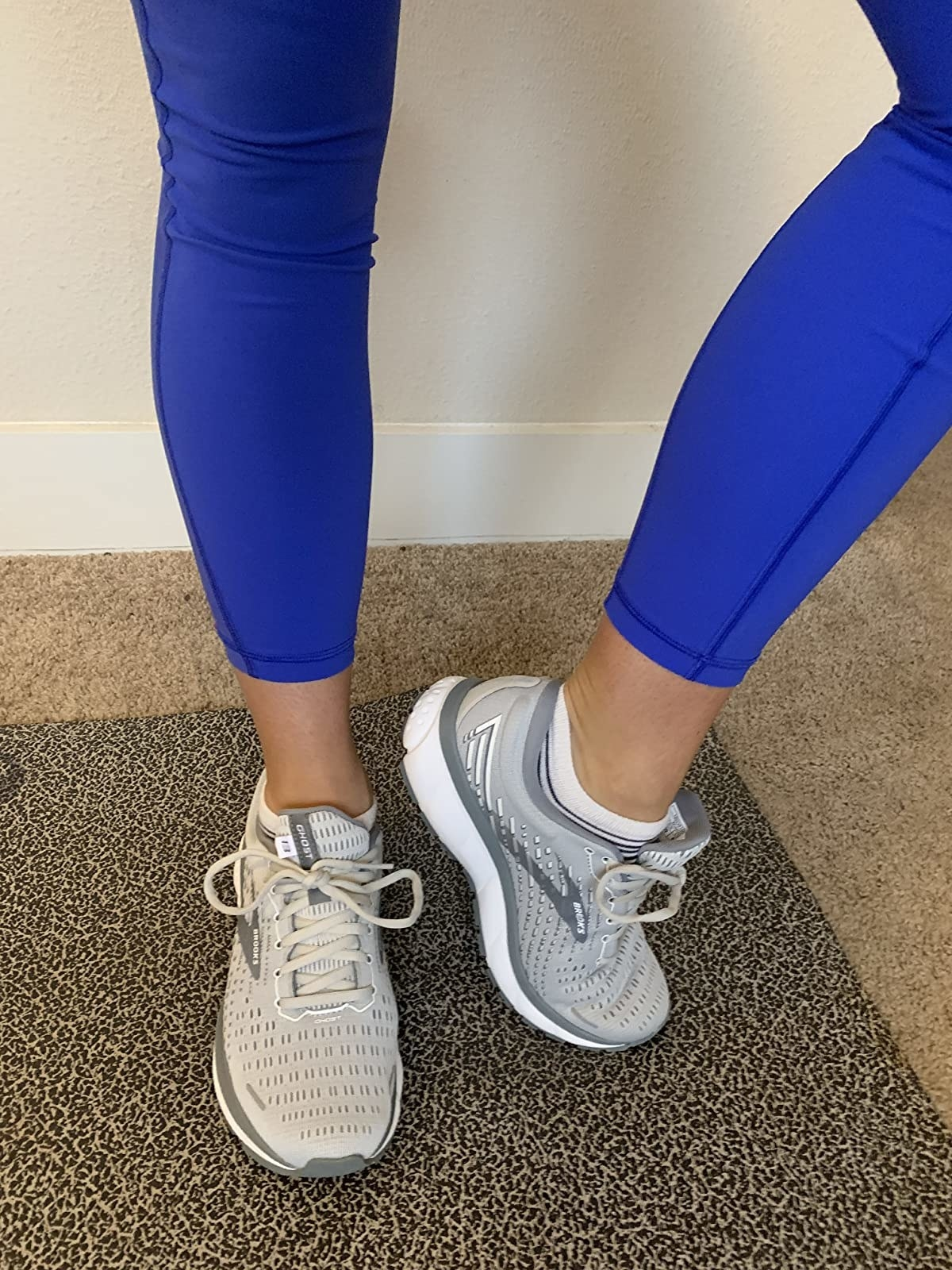 A reviewer wearing the gray sneakers that have matching laces and are covered in breathable mesh
