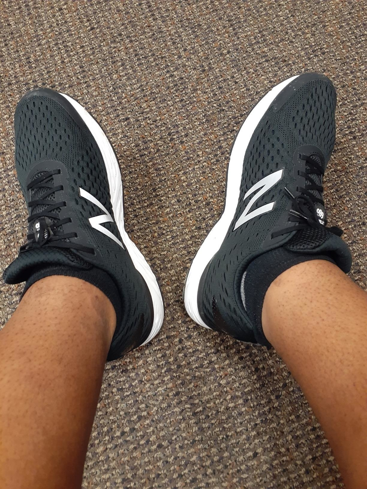 """A reviewer wearing the black shoes with a white """"N"""" and breathable mesh fabric covering the shoes"""