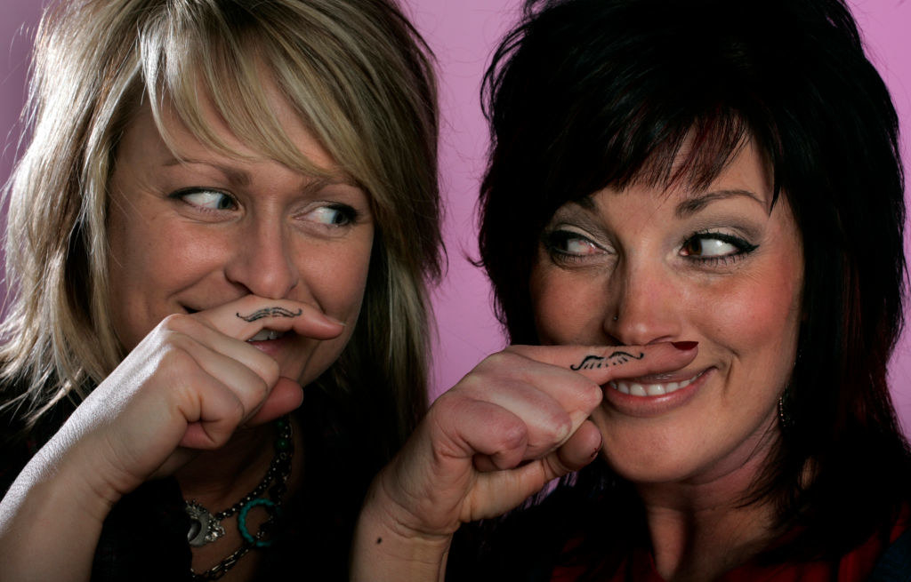 Two women smiling while having their fingers tattooed with mustaches under their nose