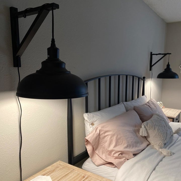 a reviewer photo of a bed framed by wooden brackets with the lights wrapped around them and plugged in behind the bedside tables
