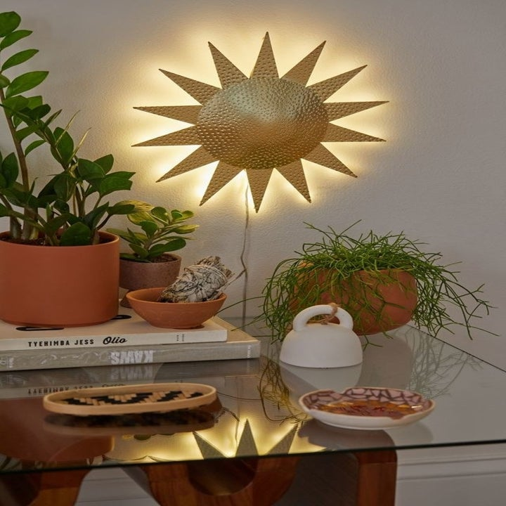 a sun-shaped wall sconce hanging on the wall behind a table covered with plants