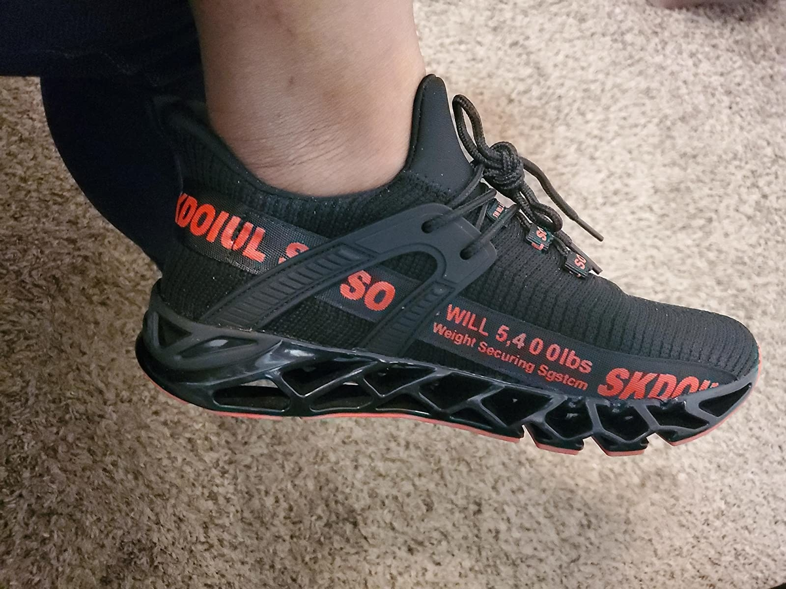 The black sneakers with red writing along the side, black reinforcements, and a partially open bottom