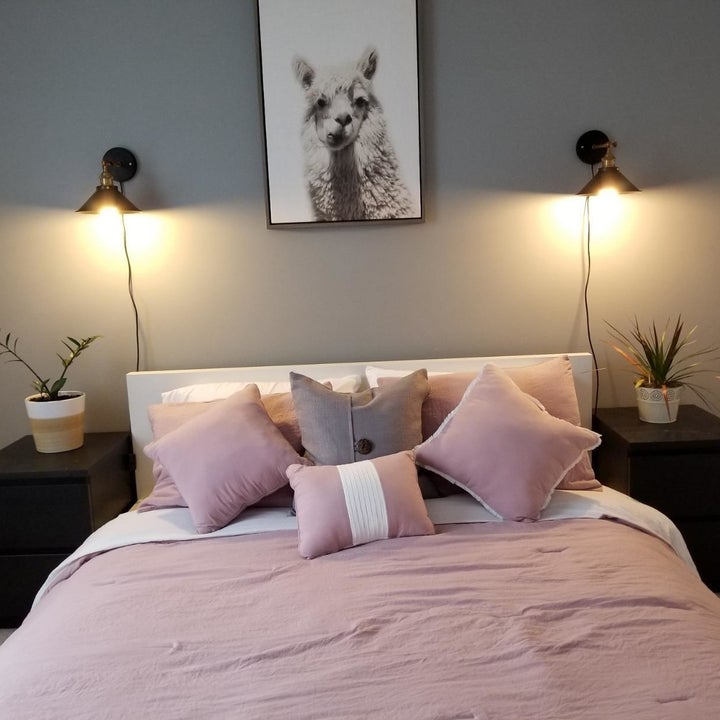 a bed framed by a pair of illuminated plug-in wall sconces