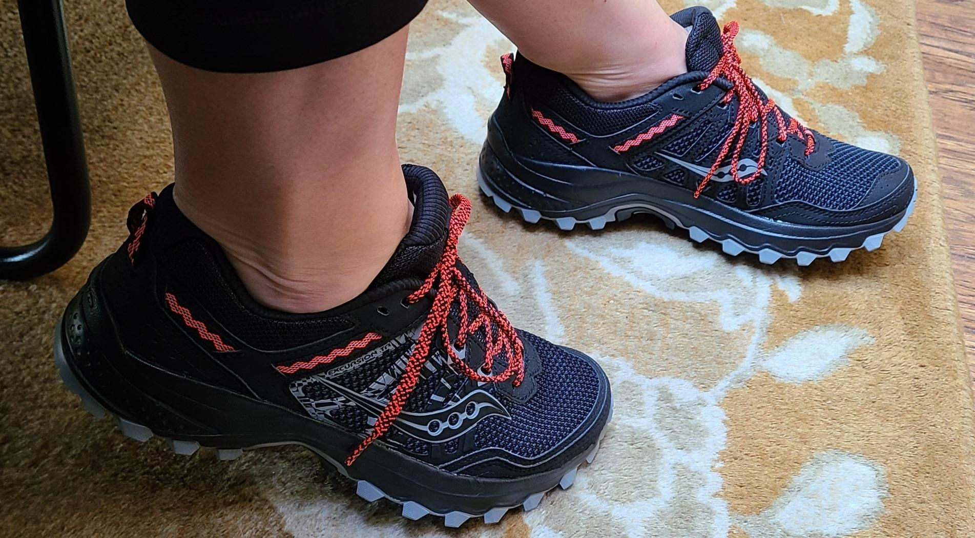 A reviewer wearing the durable sneakers with laces and a textured bottom that prevents slipping
