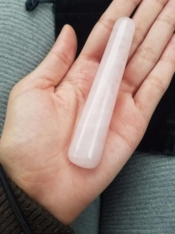 Reviewer holding the hand-sized crystal dildo