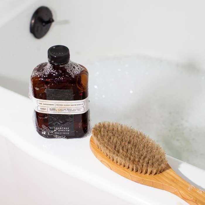 a amber bottle of bath syrup on the edge of a bathtub