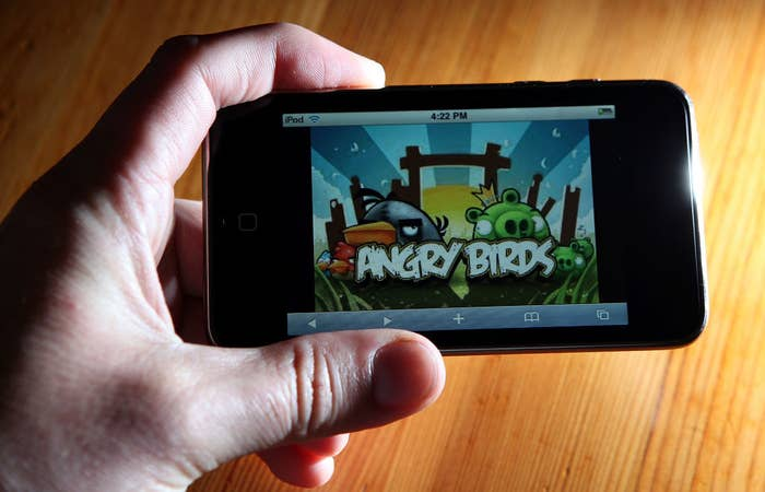 A person holding an iPhone with the Angry Birds on it