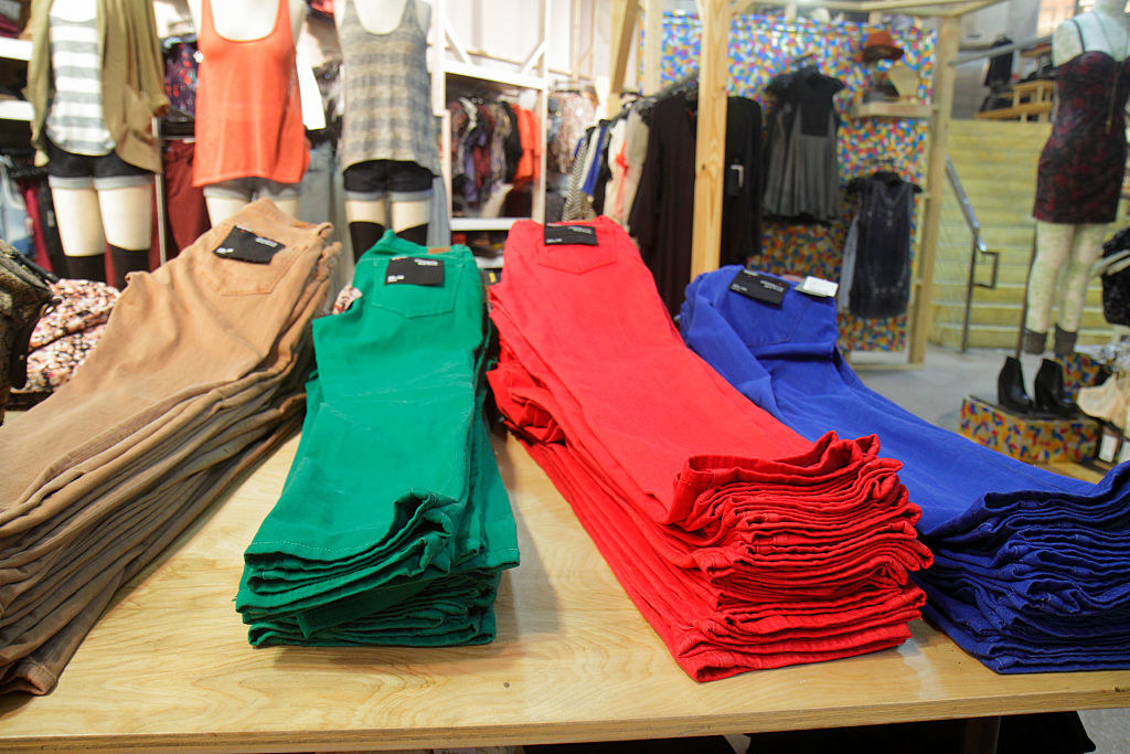 Brown, green, red, and violet skinny jeans on a display table inside an Urban Fitters