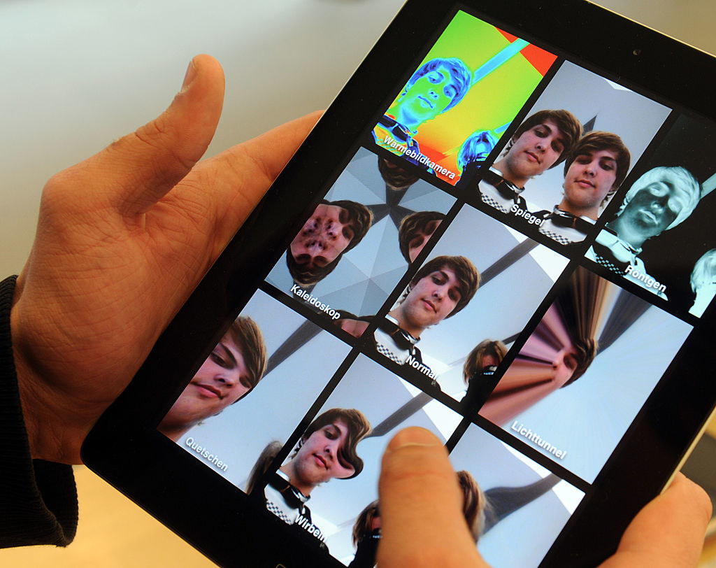 A photo of a guy playing with filters while taking selfies with an iPad