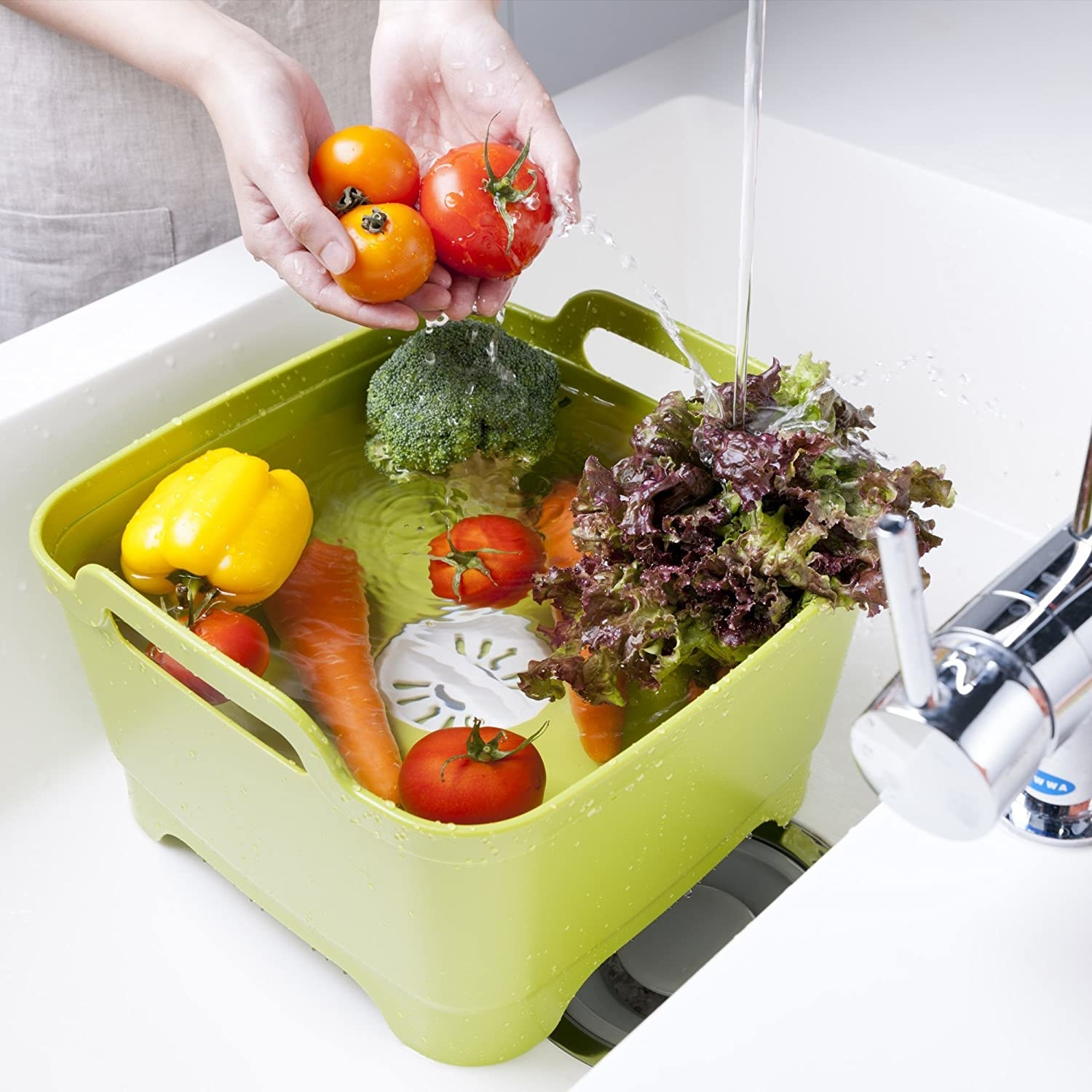 The dish tub filled with veggies in a sink
