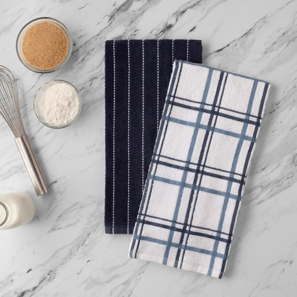 navy striped hand towel and white plaid hand towel on a counter next to cooking ingredients