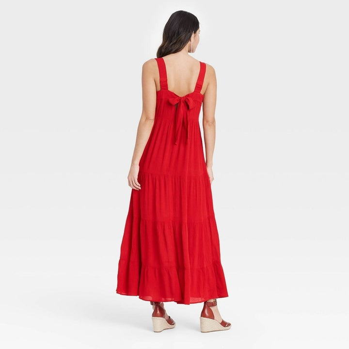 Model wearing red dress with tiered skirt, stops past the knees