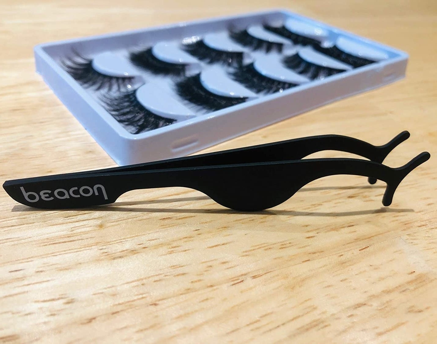 The applicator next to a box of lashes