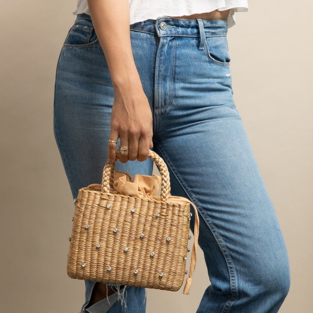 model holding the straw tote with jewels on it