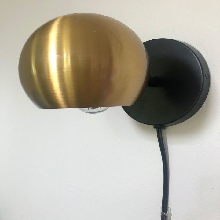 a reviewer photo of a gold-tone orb wall sconce with a black cord hanging from it