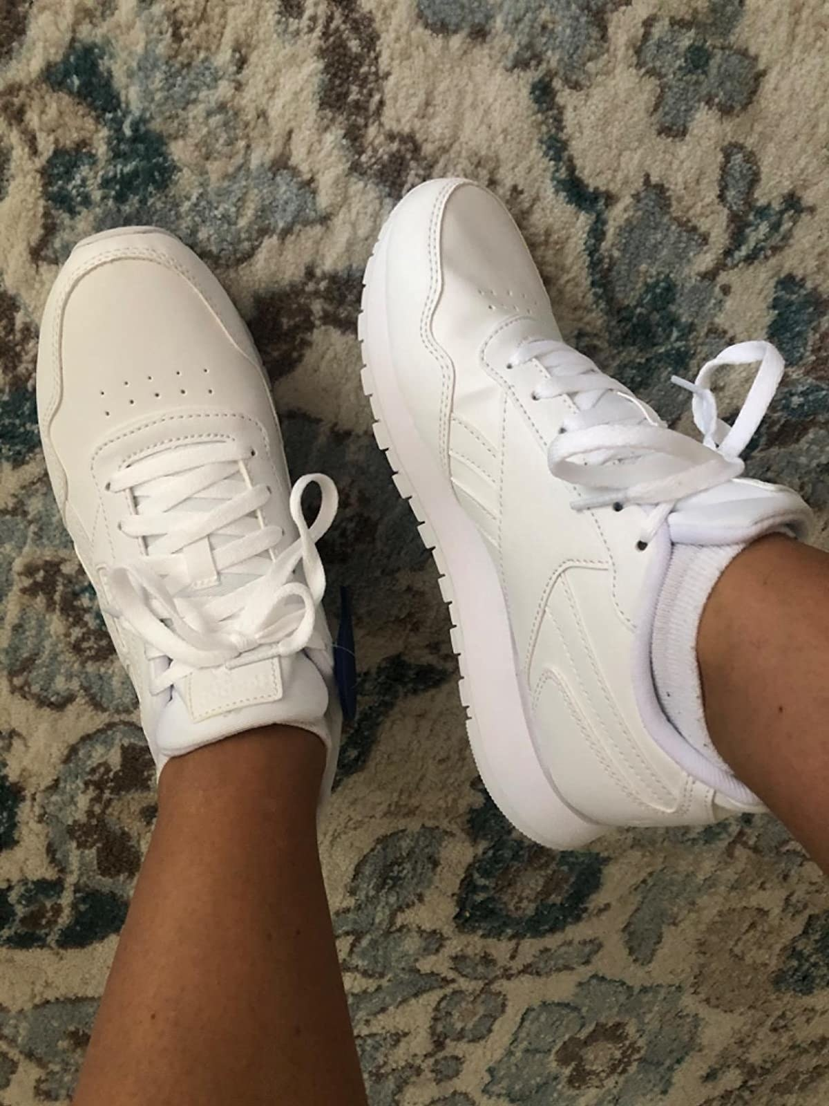 A reviewer wearing the white sneakers with matching laces and a thick bottom