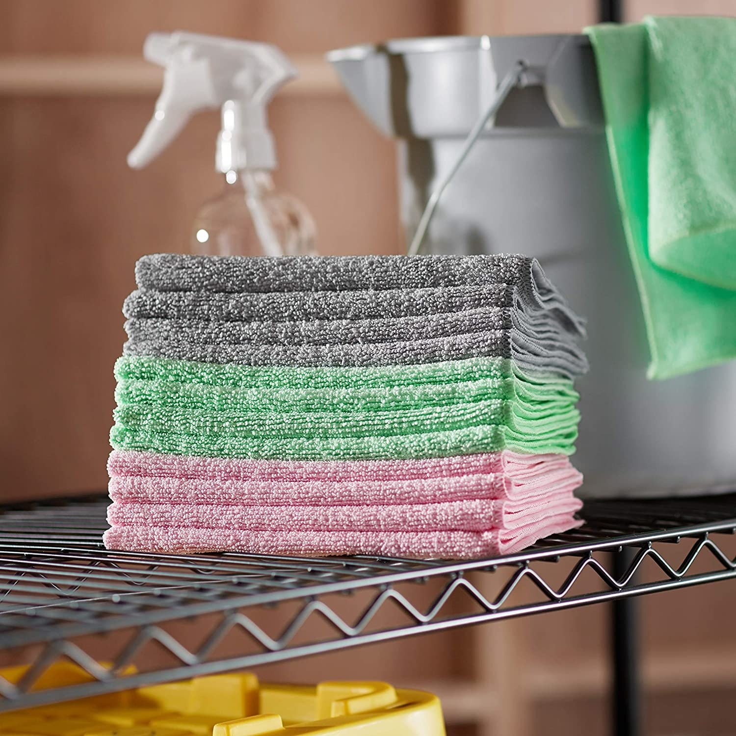 A stack of the grey, green, and pink microfiber cloths on a shelf next to cleaning supplies
