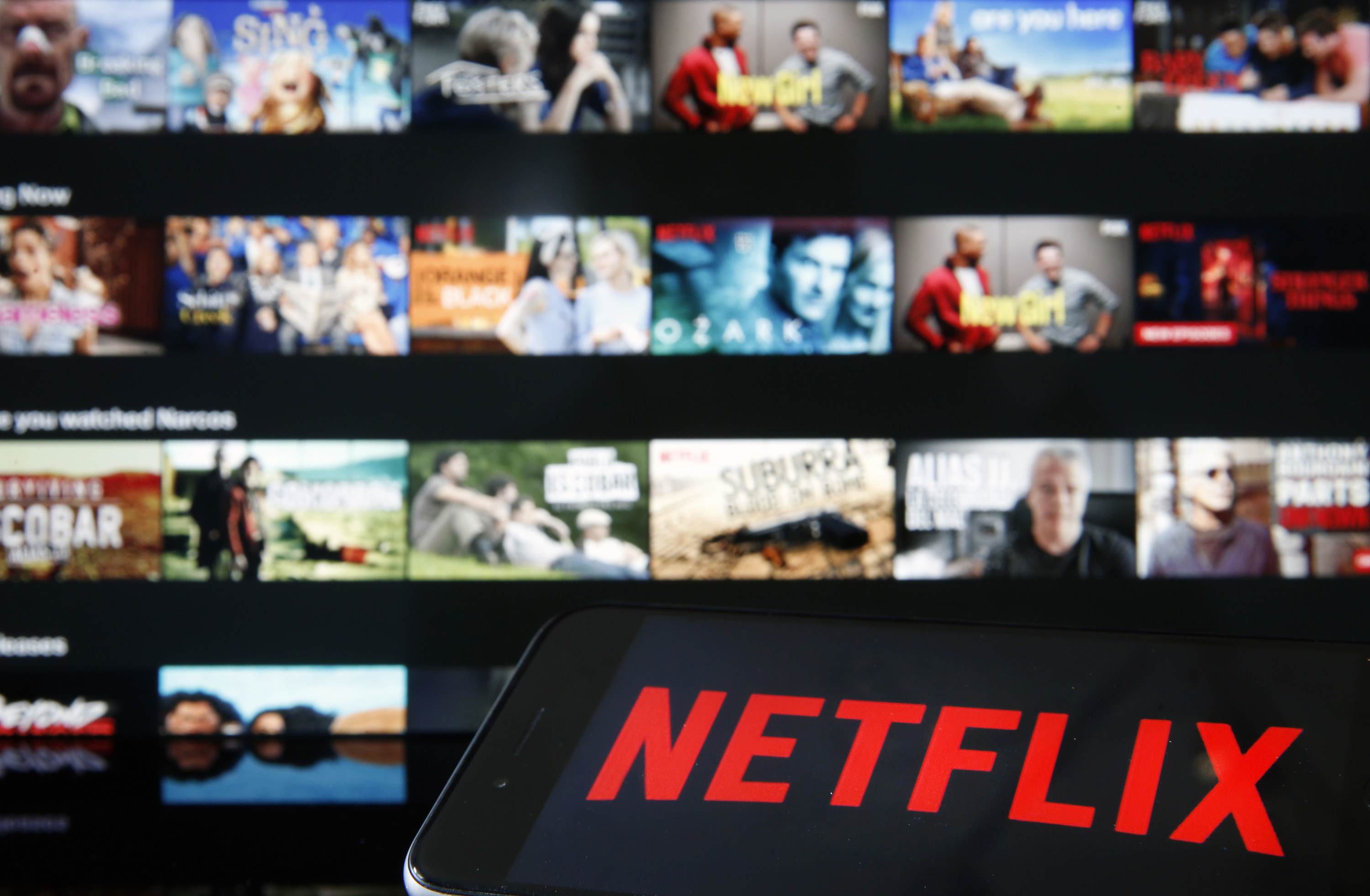 A smartphone with the Netflix screen loading in front of the Netflix movie selection screen