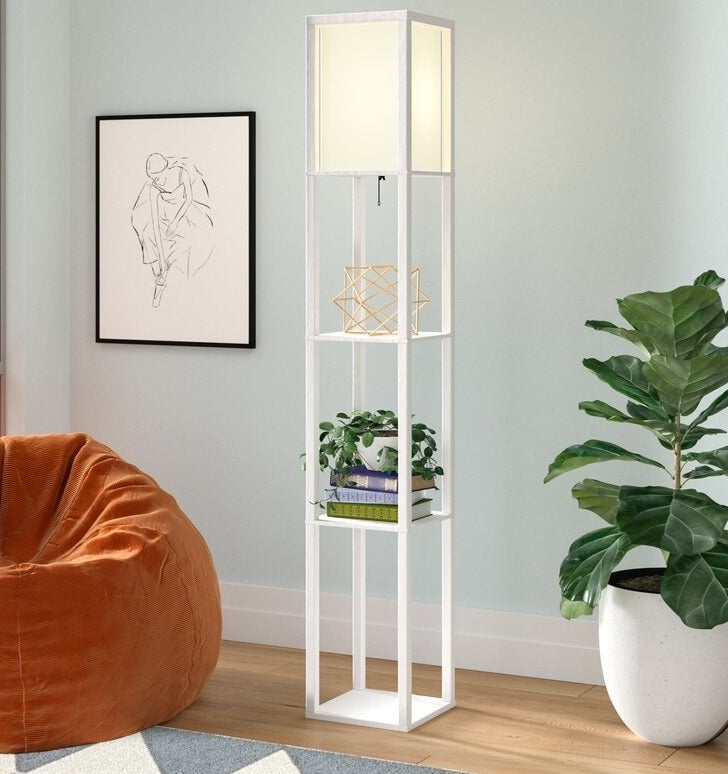 a two-tiered column floor lamp with books sitting on each platform