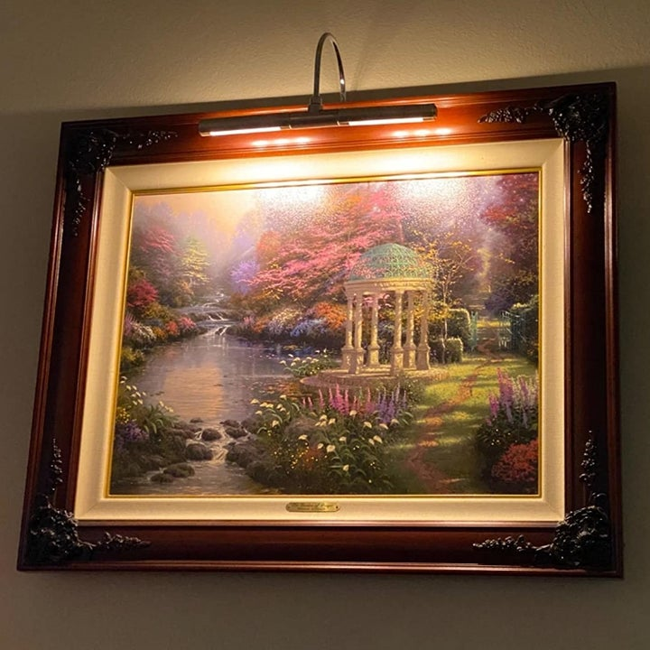 a reviewer photo of a framed painting with the picture light mounted on the frame