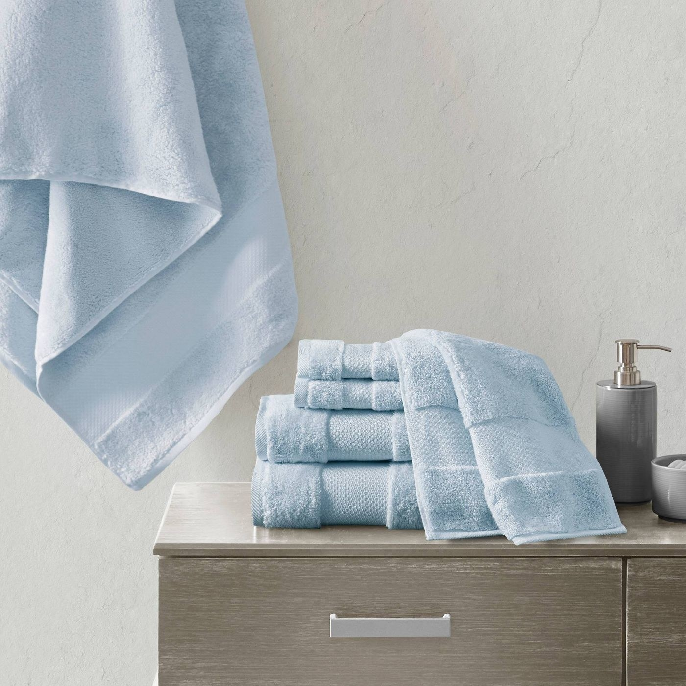 the light blue Turkish Cotton Bath Towel Set folded and stacked on a bathroom counter