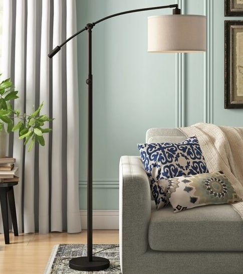 a floor lamp with an arched arm with a lamp shade on the end hanging over a couch