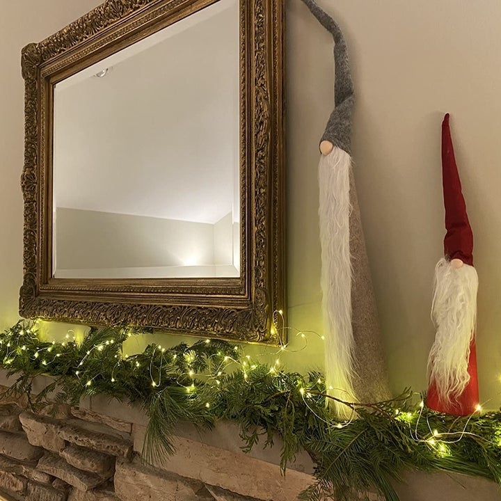 a reviewer photo of the fairy light woven around garland on a mantel