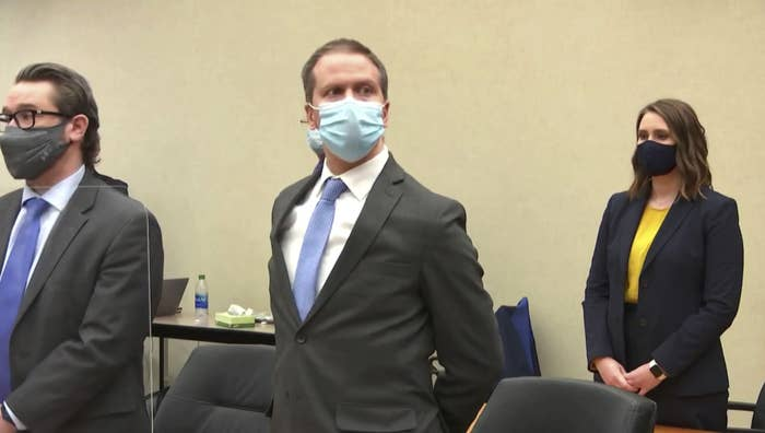 Derek Chauvin wears a face mask and has his hands cuffed behind his back in court