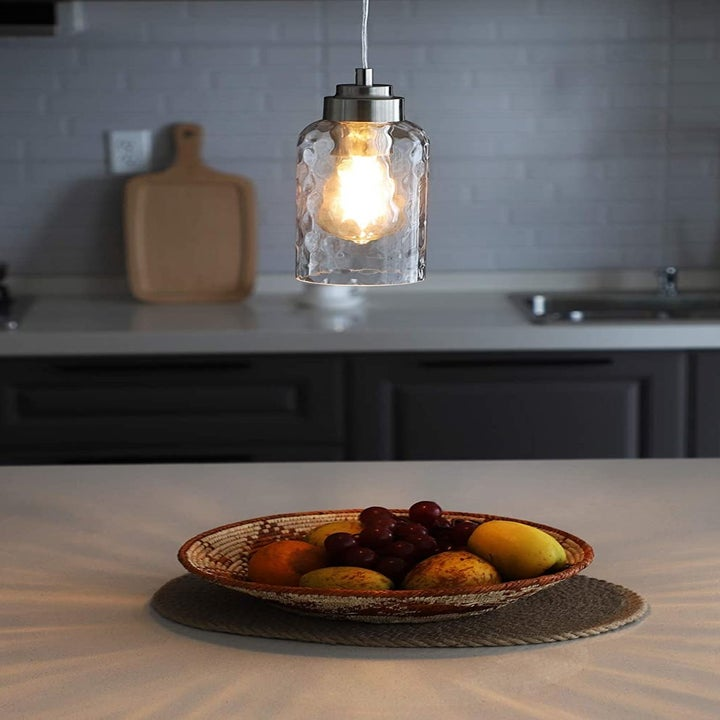 a pendant hanging over a countertop with a bowl of fruit sitting on it