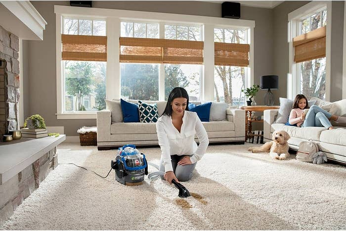 Model using the carpet cleaner to remove a brown stain on a white carpet
