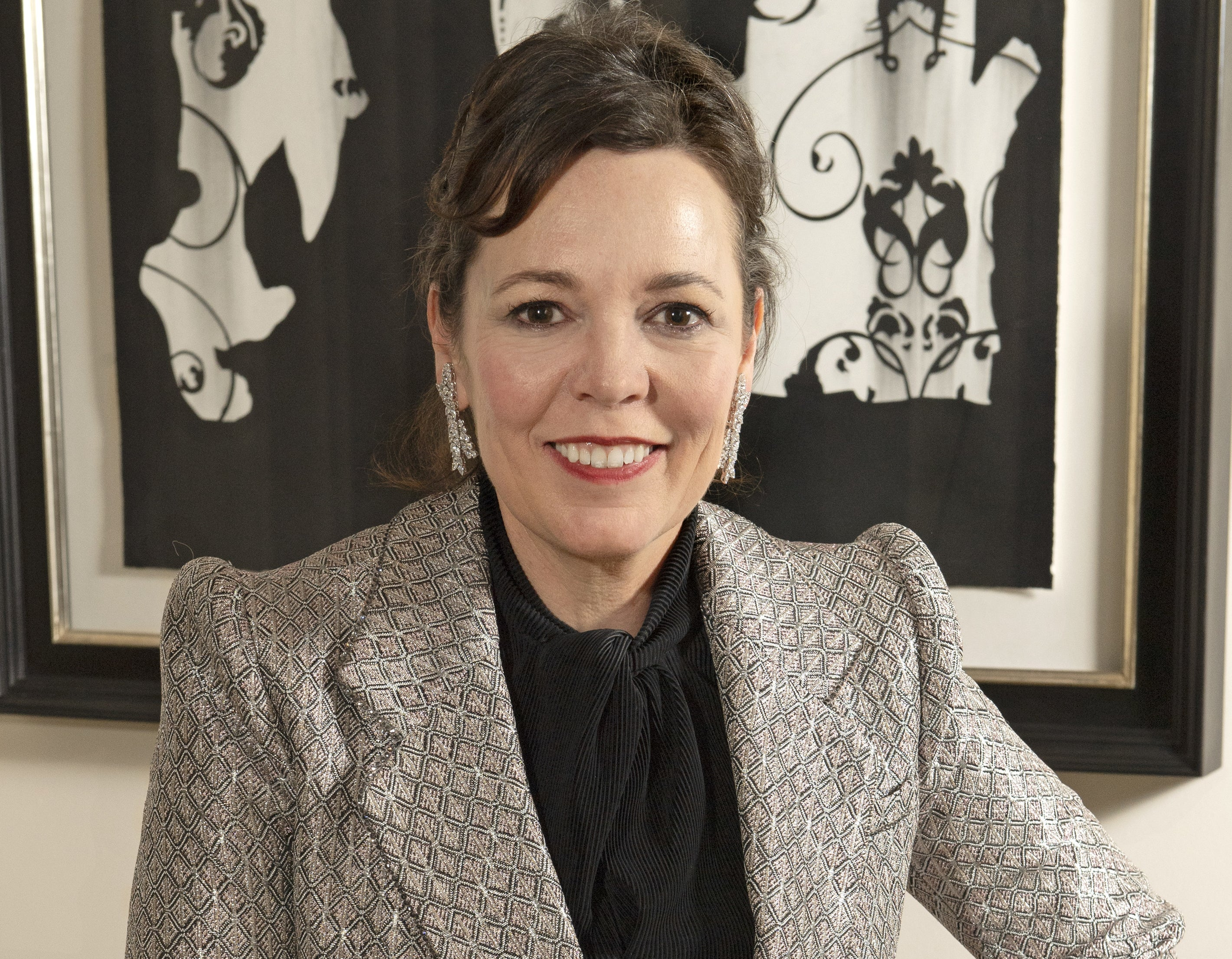 Olivia Colman smiles while sitting in a living room