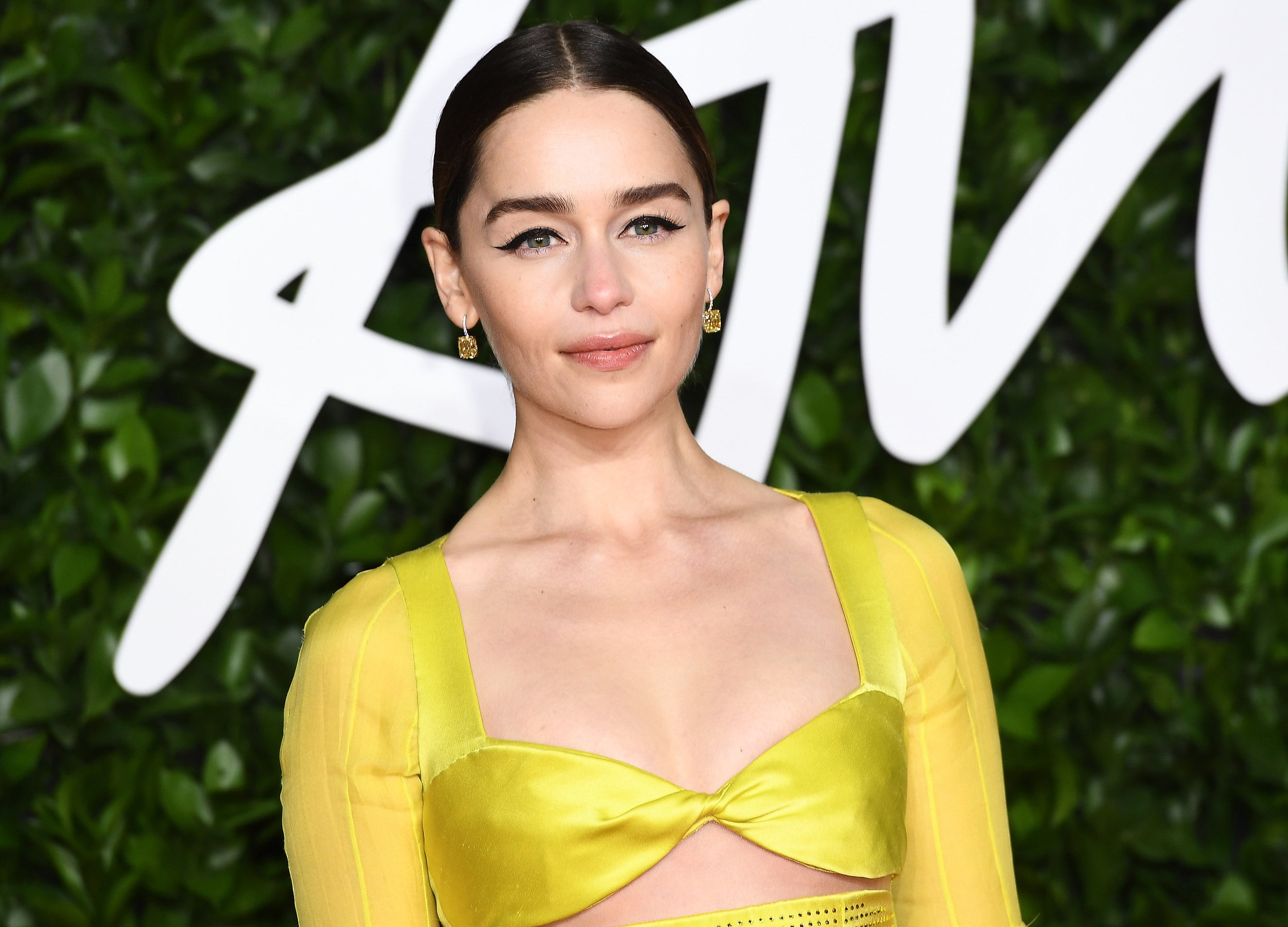 Emilia Clarke wears a bright yellow dress to an event