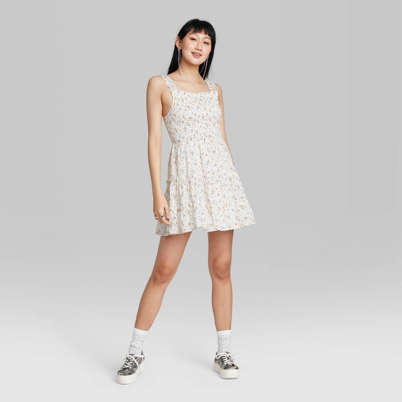 Model wearing white mini dress with floral patter, has a tiered hem skirt