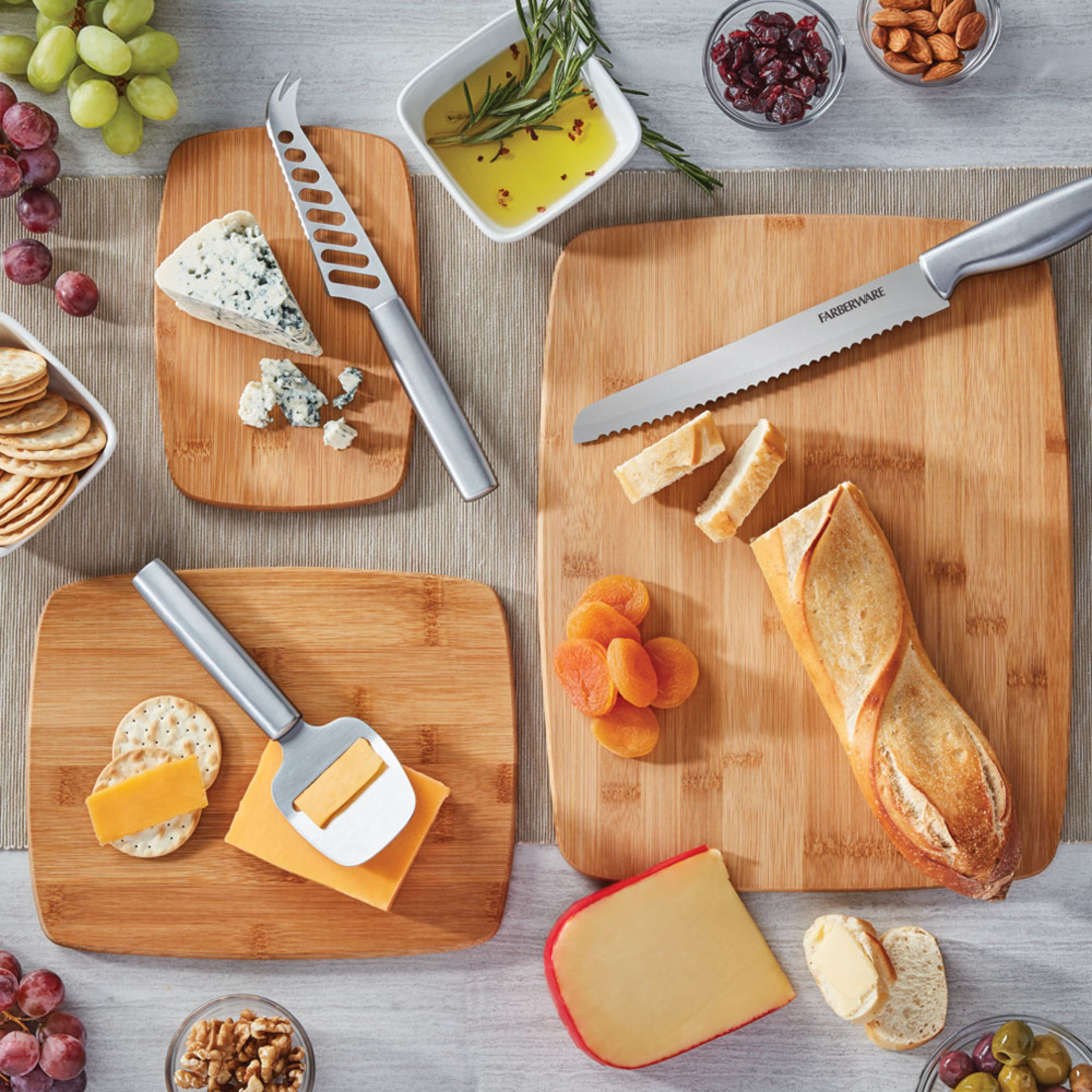 three bamboo cutting boards of various sizes with cheese, bread, and knives on top