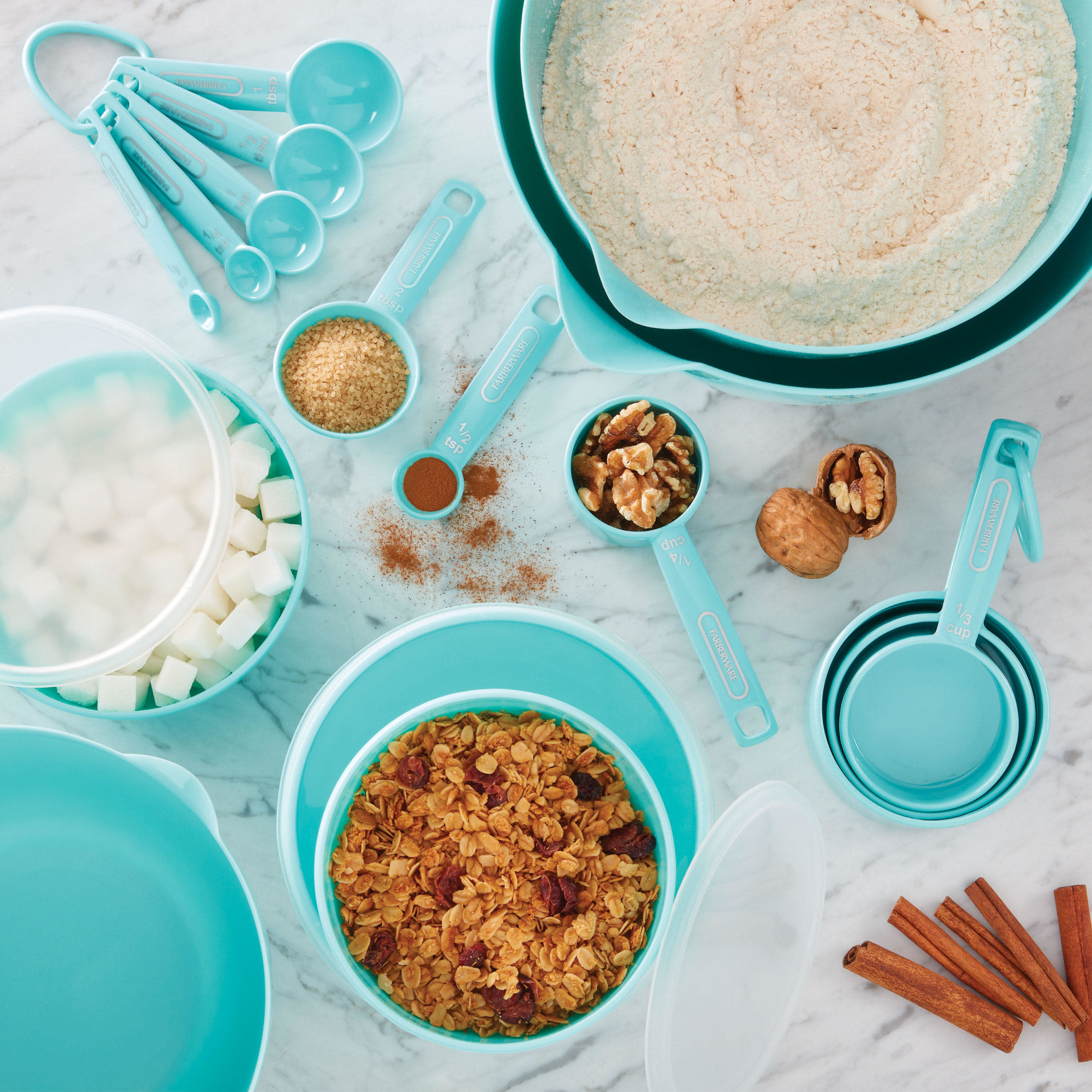 overhead shot of light blue mixing bowls and measuring spoons with ingredients on a table