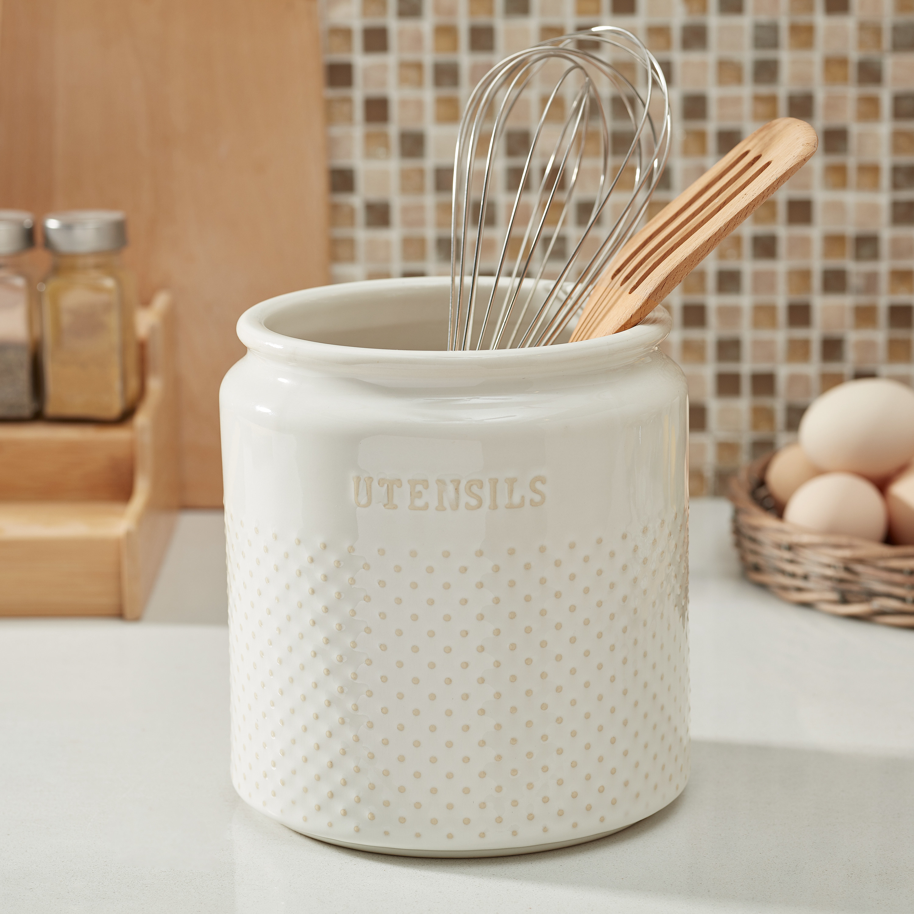 """white dotted ceramic utensil holder with """"utensils"""" printed on the front, on a counter"""