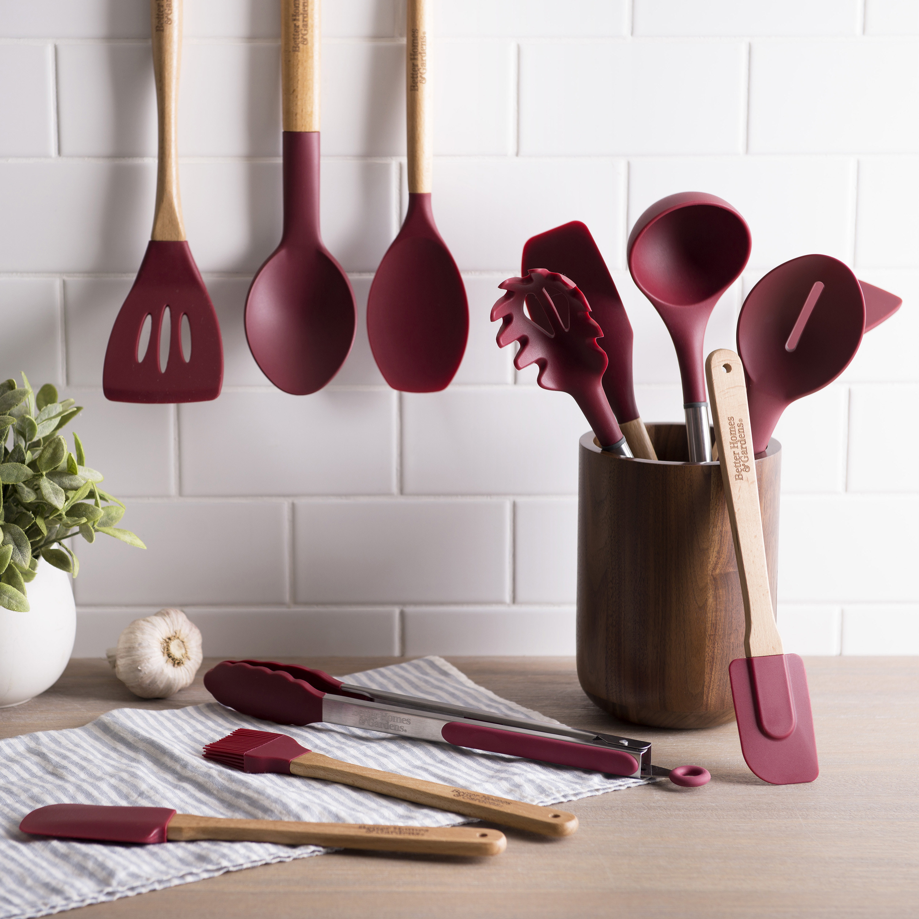 merlot-colored 12-piece silicone utensil set on a table, hanging, and in a utensil jar