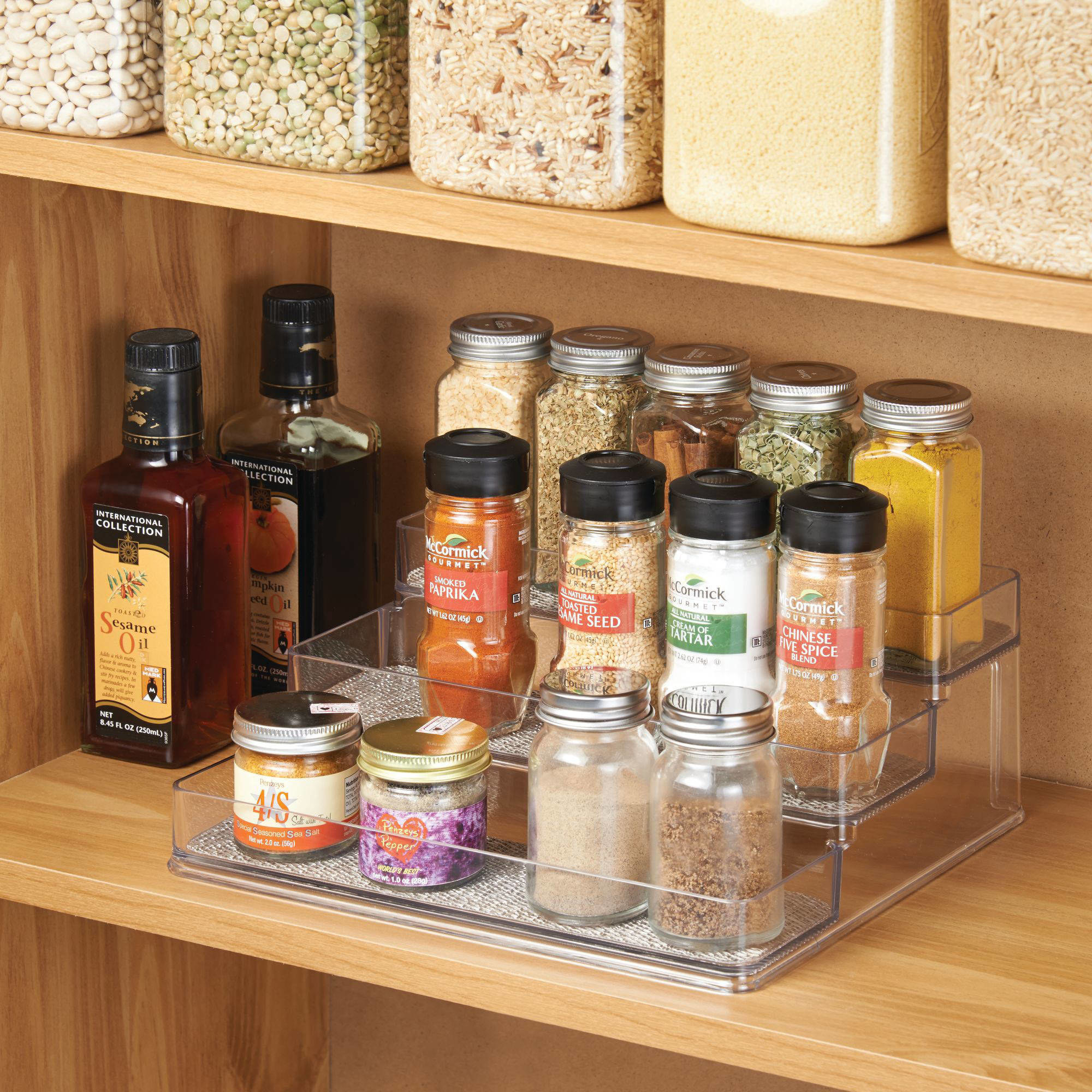 clear three-tiered spice rack organizer with jars of spices, on a shelf