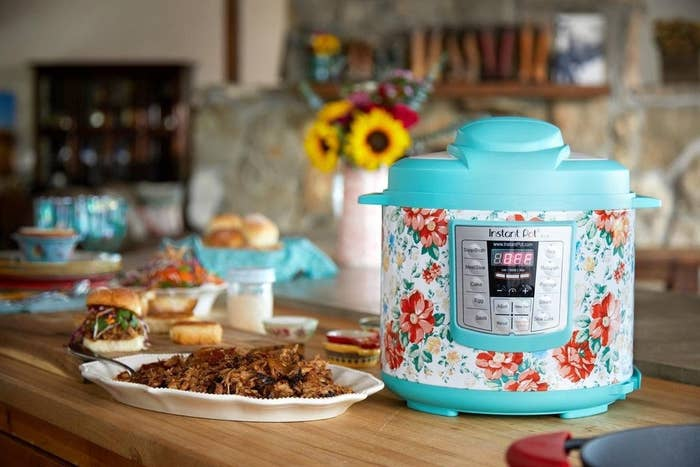 The Instant Pot, which has push-button settings, a floral print, and blue plastic top