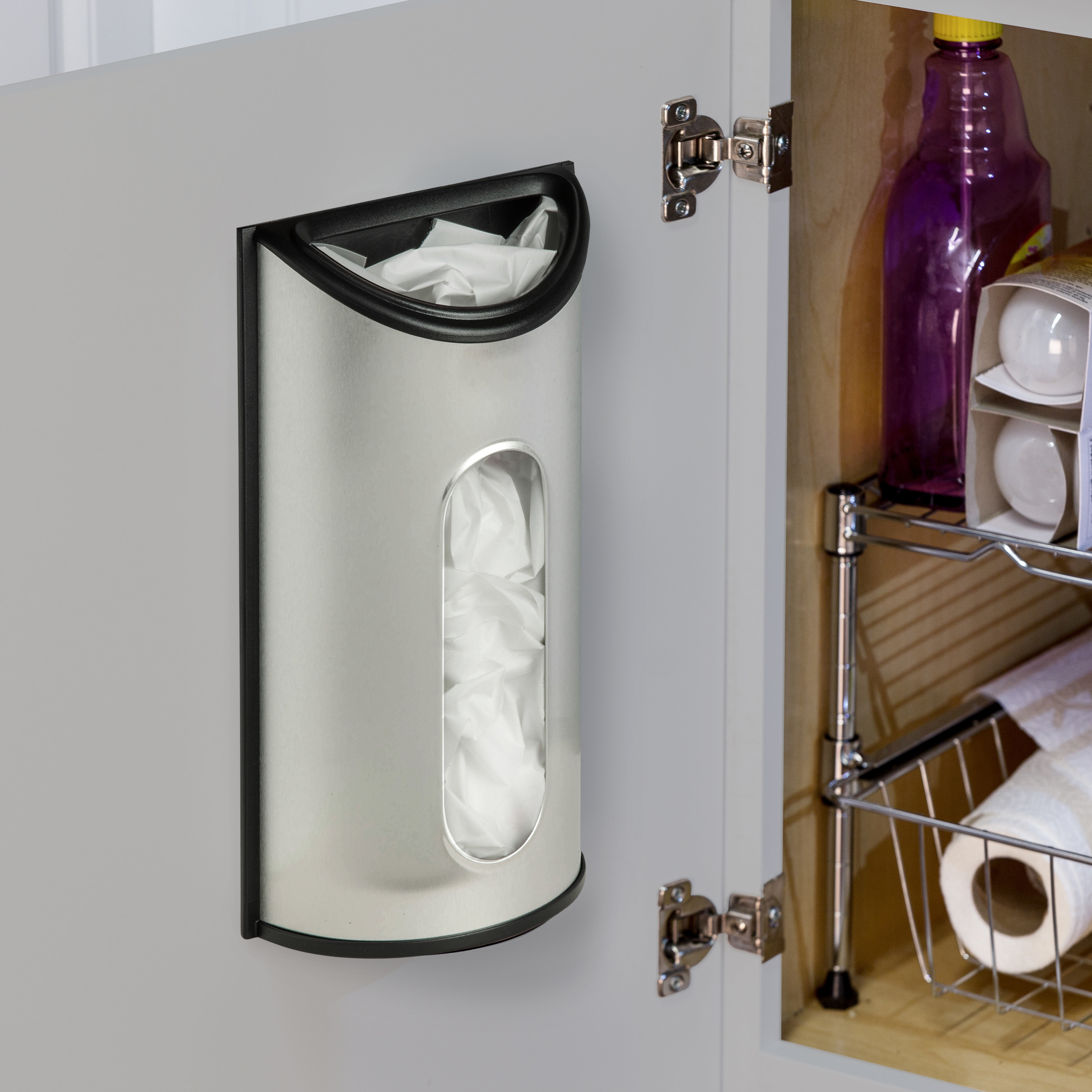 stainless steel plastic bag dispenser mounted on the inside of a cabinet door