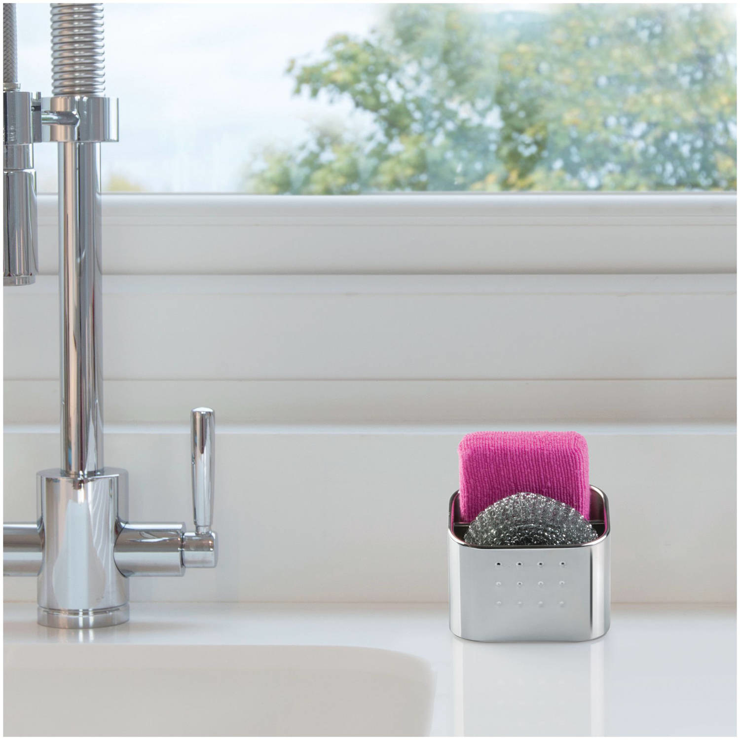 stainless steel sink organizer on a counter next to sink, with two sponges inside