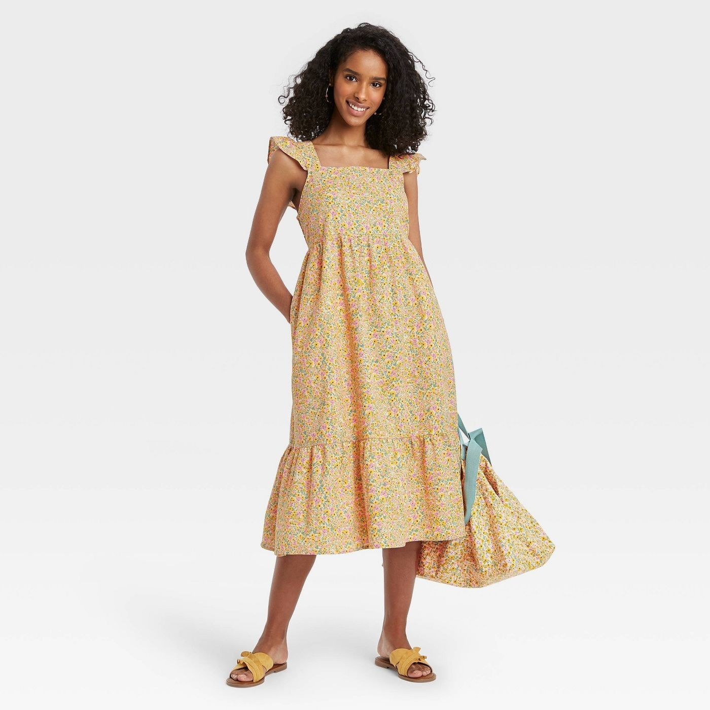 Model wearing yellow floral dress with hemmed skirt