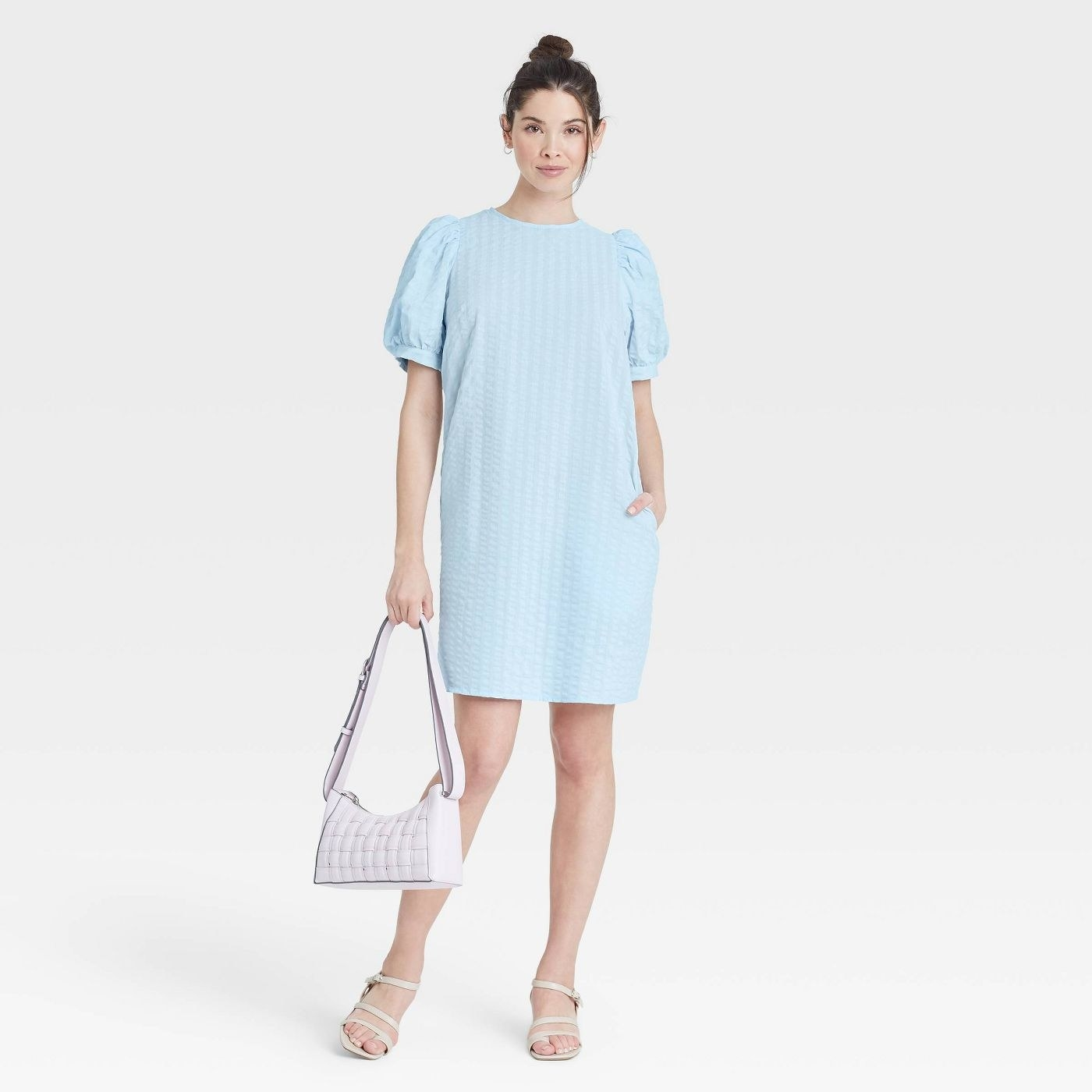 Model wearing blue dress with puff sleeves, goes past the thighs