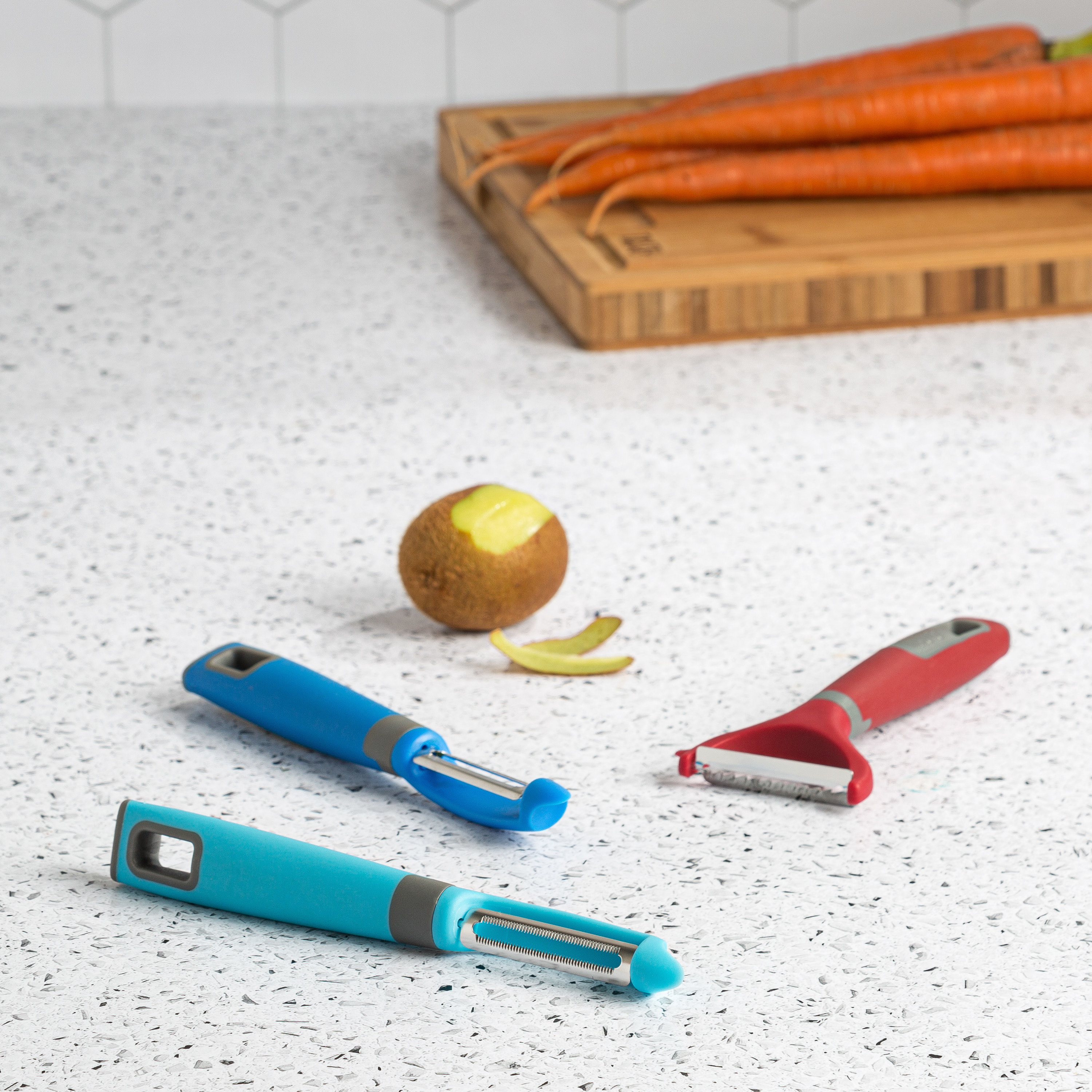 three different peelers on a table next to a kiwi and cutting board