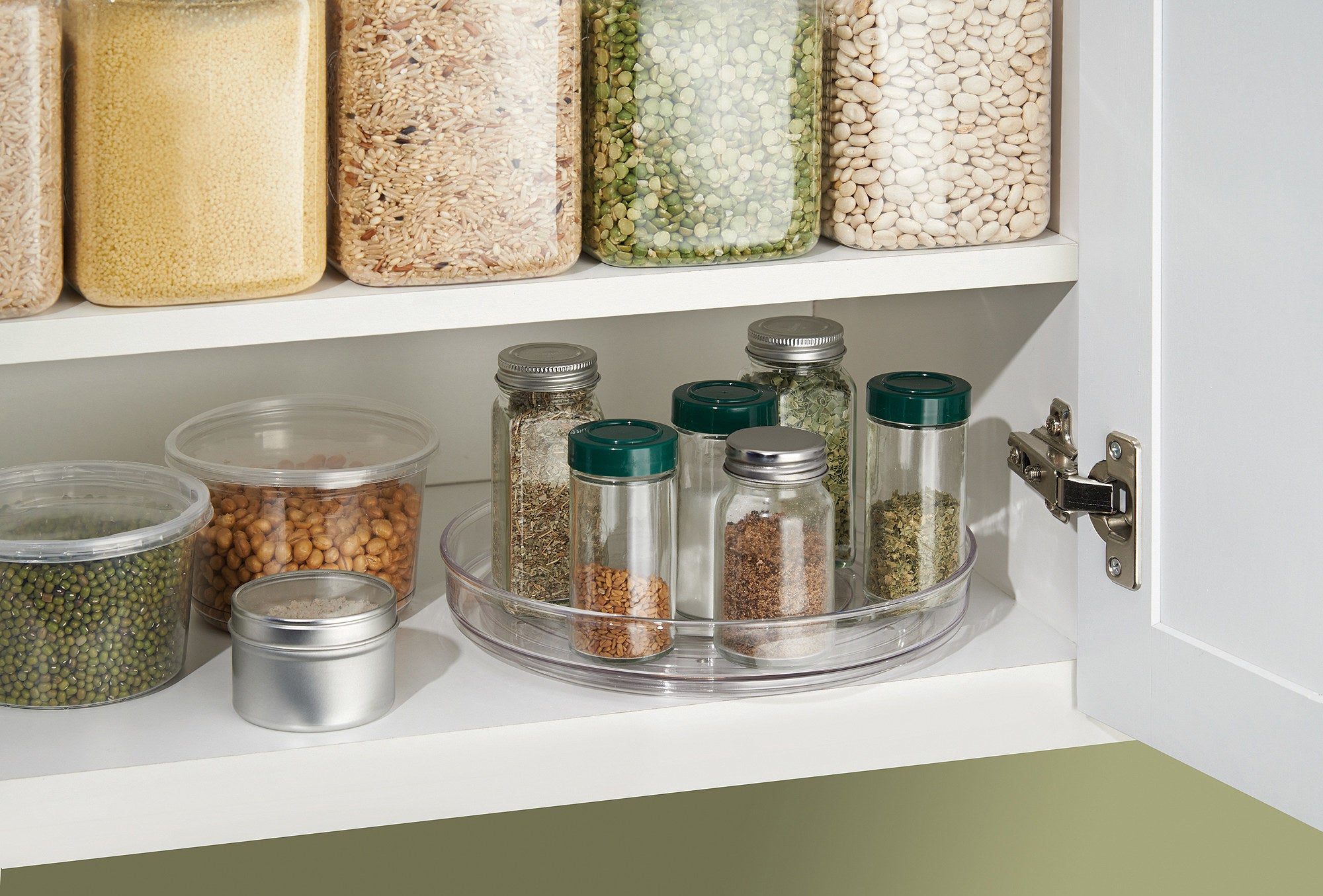 clear turnable holding spice jars on the bottom shelf of a cabinet