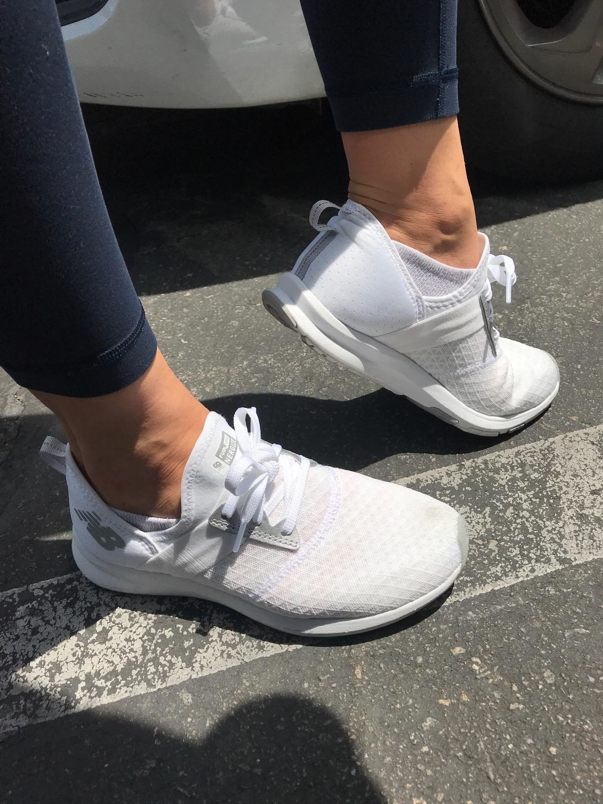 A reviewer wearing the shoes in white with a mesh, breathable exterior