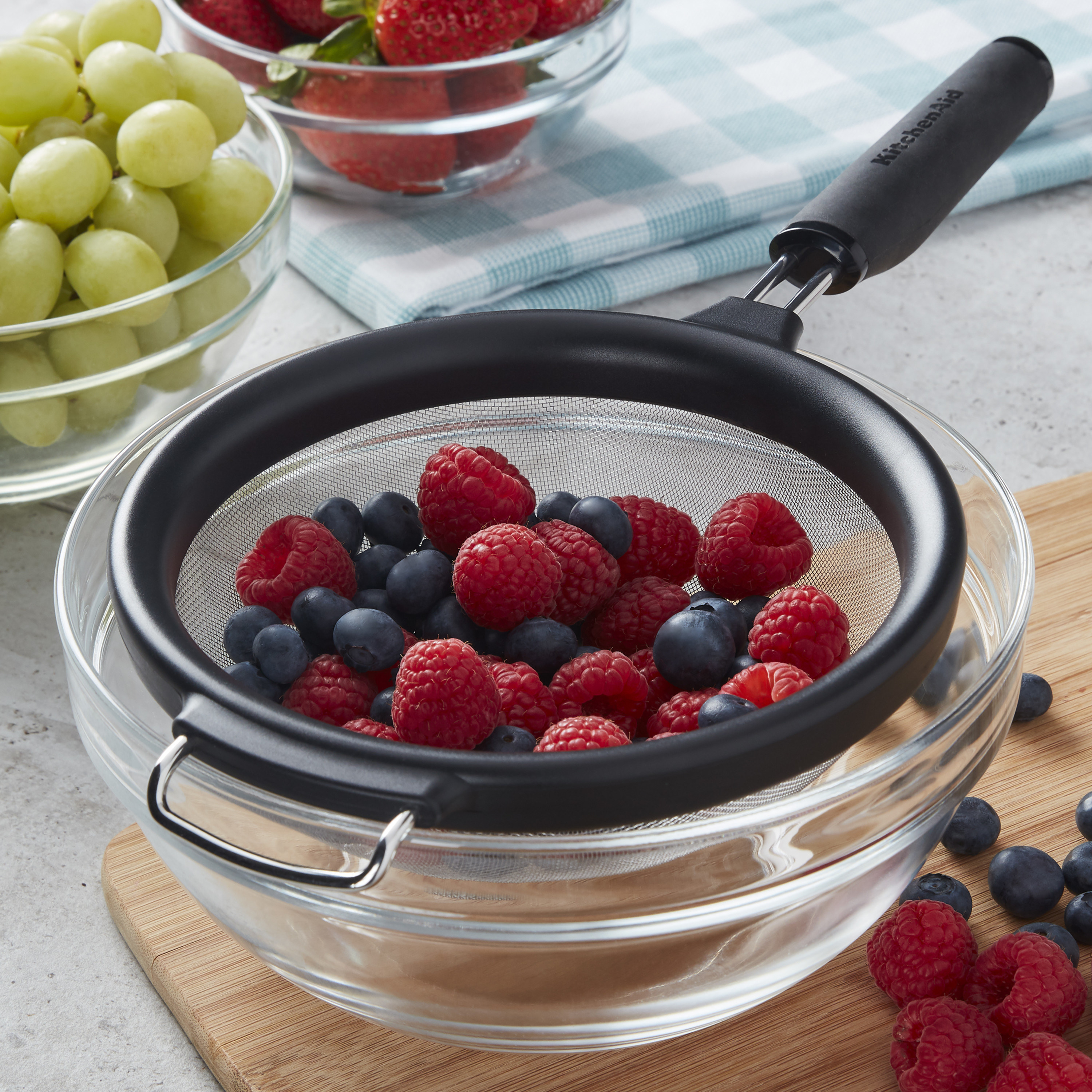 stainless steel mesh strainer with a handle, with fresh berries inside