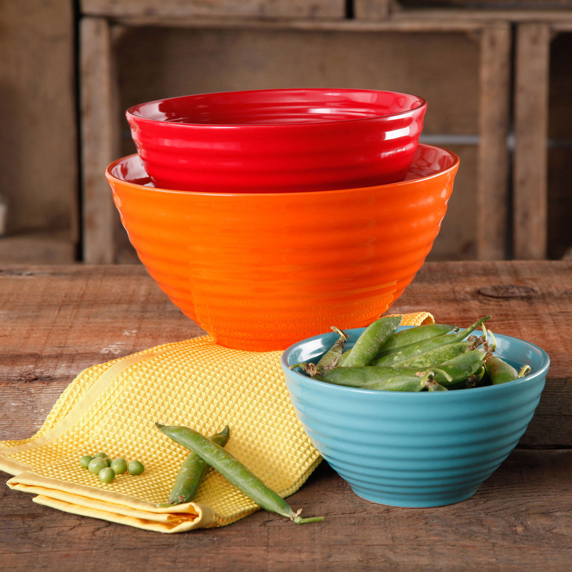 An orange and red ceramic bowl stacked, and a small ceramic bowl with snap peas inside